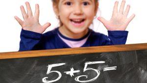 Girl Holding Up Ten Fingers Behind Chalkboard